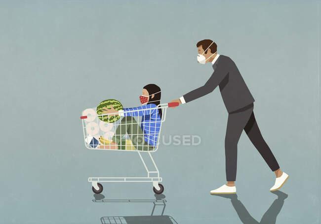 Homem com máscara de rosto protetora empurrando filha no carrinho de compras — Fotografia de Stock