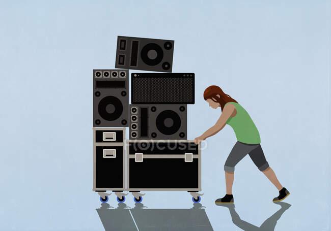 Женщина толкает динамики и музыкальное оборудование на тележку — стоковое фото