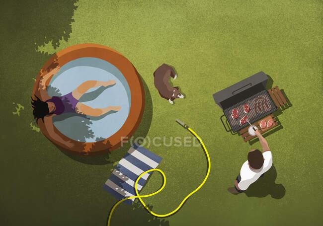 Женщина отдыхает в детском бассейне, а мужчина барбекю на заднем дворе — стоковое фото