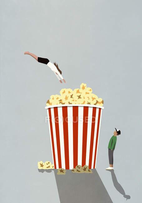 Женщина ныряет в ванну с попкорном в большом кинотеатре — стоковое фото