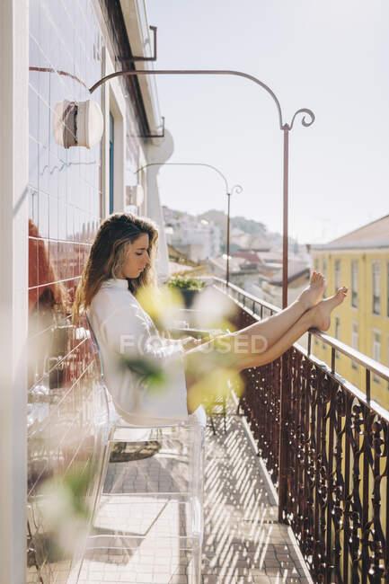Giovane donna che si rilassa sul balcone soleggiato appartamento, Lisbona, Portogallo — Foto stock