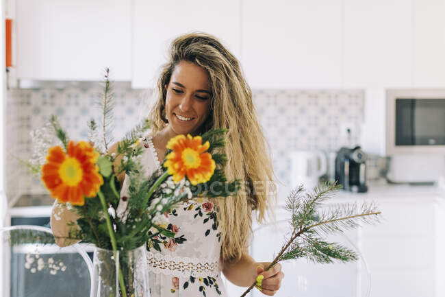 Smiling young woman arranging flower bouquet in kitchen — Stock Photo