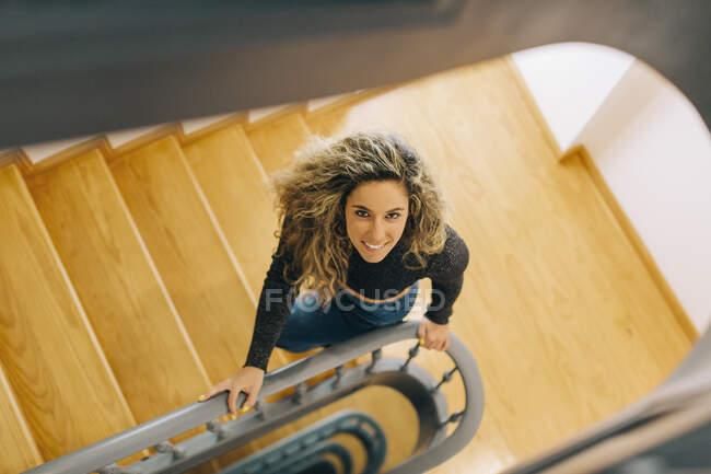 Ritratto giovane donna sorridente su scala in legno — Foto stock