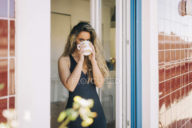 Portrait young woman drinking coffee in patio doorway — Stock Photo