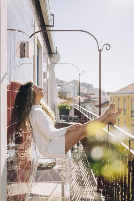 Serena giovane donna che si rilassa sul balcone soleggiato appartamento, Lisbona, Portogallo — Foto stock