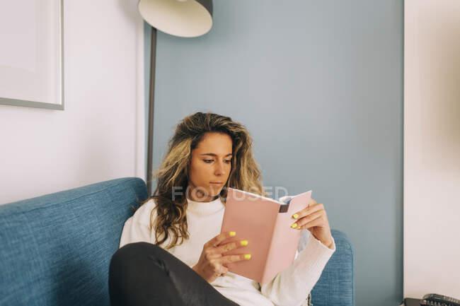 Giovane donna che legge libro sul divano — Foto stock