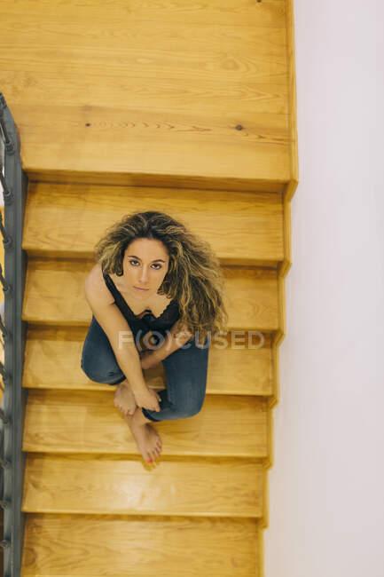 Ritratto bella giovane donna seduta su gradini di legno — Foto stock
