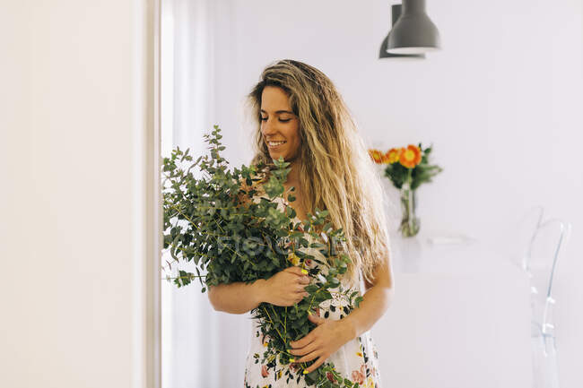 Sorridente giovane donna in possesso di mazzo di eucalipto fresco — Foto stock