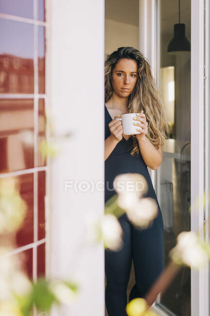 Portrait young woman drinking tea in patio doorway — Stock Photo