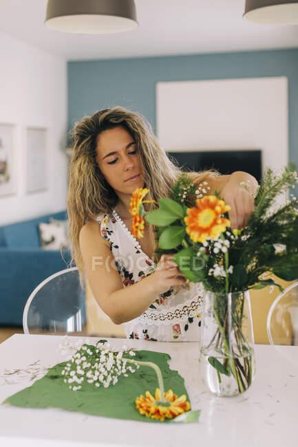 Giovane donna che organizza mazzo di fiori in cucina — Foto stock