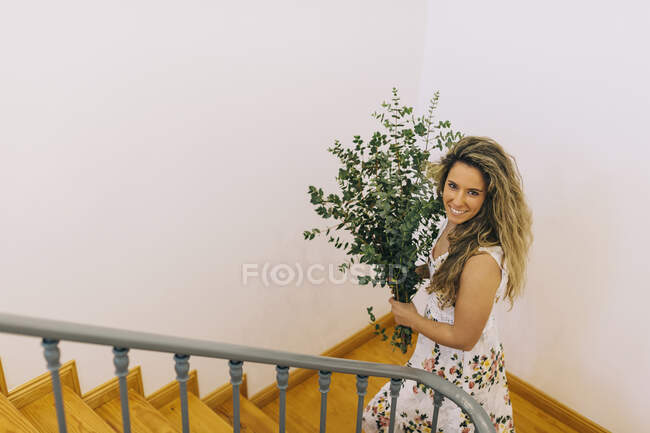 Portrait smiling woman carrying bunch of eucalyptus on staircase — Stock Photo