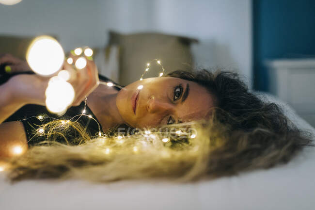 Portrait serene young woman with string lights on bed — Stock Photo