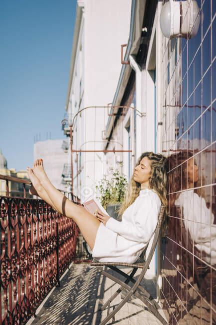 Serena giovane donna che legge libro sul balcone appartamento soleggiato, Lisbona, Portogallo — Foto stock