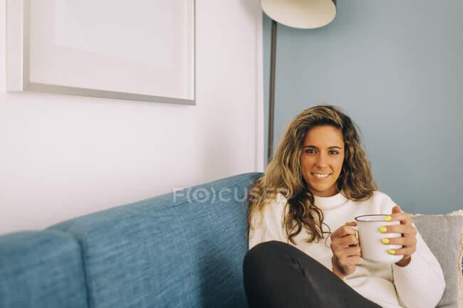 Ritratto sorridente giovane donna che beve caffè sul divano — Foto stock