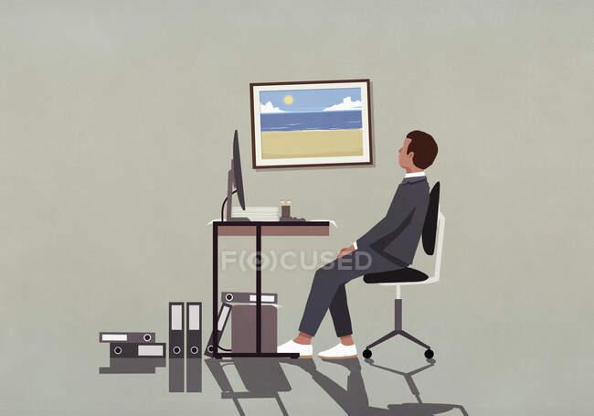 Empresario en escritorio de la oficina mirando la fotografía de la playa en la pared - foto de stock