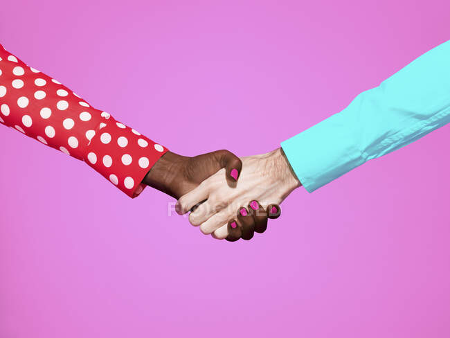 Multiethnic handshake on pink background — Stock Photo