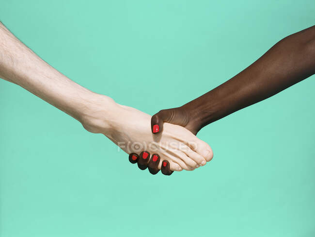 Multiethnic foot and hand shake on green background — Stock Photo