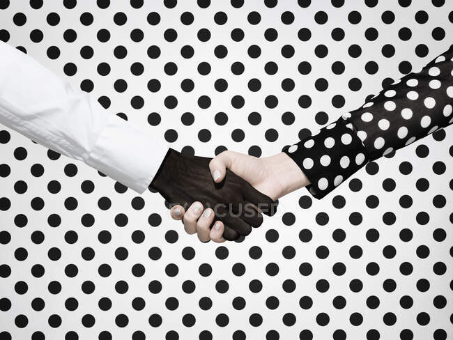 Multiethnic handshake on polka dot background — Stock Photo