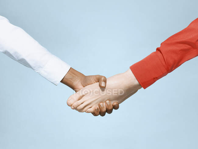 Hand shaking bare foot on blue background — Stock Photo