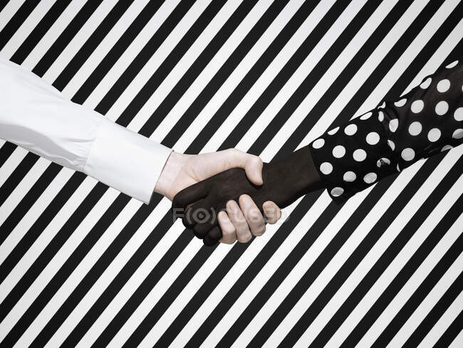 Multiethnic handshake on striped background — Stock Photo