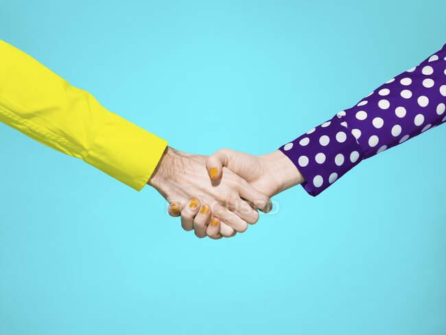Vibrant handshake on turquoise background — Stock Photo