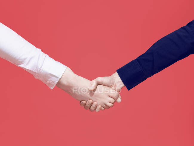Hand shaking barefoot on red background — Stock Photo