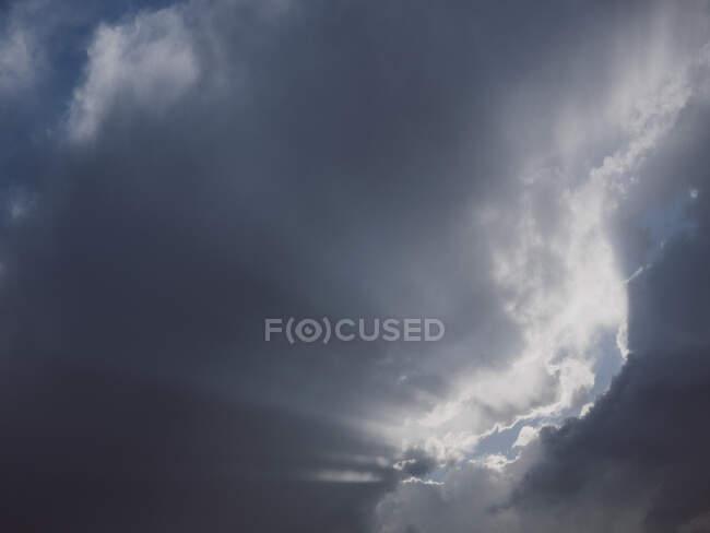Cielo del atardecer con nubes y luz solar - foto de stock