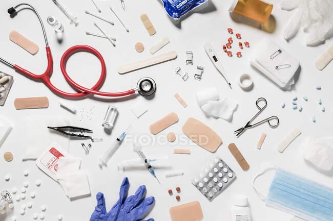 Seringas médicas, frascos de vidro, comprimidos, estetoscópio espalhados no fundo branco — Fotografia de Stock