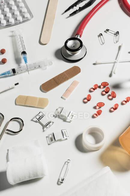 Медицинские шприцы, стеклянные бутылки, таблетки, стетоскоп разбросанный на белом фоне — стоковое фото