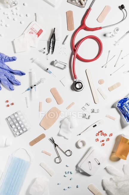 Медичні шприци, скляні пляшки, таблетки, стетоскоп, розкиданий на білому тлі. — стокове фото