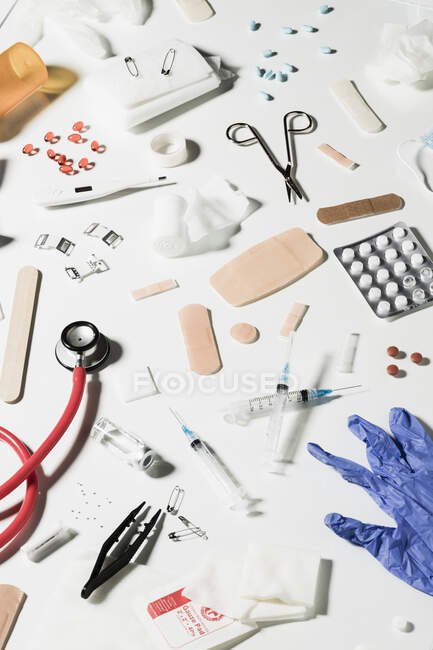 Jeringas médicas, frascos de vidrio, pastillas, estetoscopio esparcidos sobre fondo blanco - foto de stock