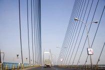 Vista del puente moderno con el carro en camino con postes de luz durante el día - foto de stock