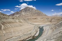 Confluence of green water of river Indus and muddy brown water of river Zanskar near Nimmu on the Leh-Kargil road with the barren Ladakh landscape in the background. Ladakh.India — Stock Photo