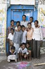 Indian children in front of closed blue door. Salunkwadi, Ambajogai, Beed, Maharashtra, India — Photo de stock