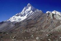 Vista dos picos de montanhas com campo chapado na inclinação durante o dia — Fotografia de Stock