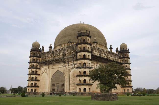 Vista laterale del tempio Gol Gumbaz sul prato erboso verde durante il giorno, Karnataka, India — Foto stock