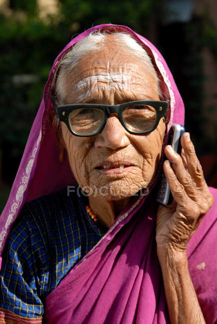 Portrait of indian rural old woman in glasses speaking on mobile phone. Lonavala, Maharashtra, India — Stock Photo