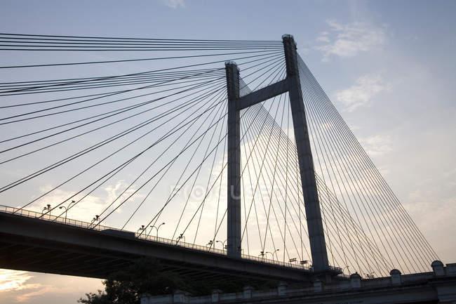 Vista de ângulo baixo da construção da ponte com fios contra céu nublado na noite — Fotografia de Stock