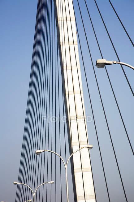 Vista de la construcción del puente con postes de luz contra el cielo azul - foto de stock