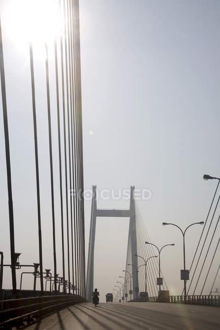 Vista del ponte moderno con fili e scooter che si muovono su strada vicino ai lampioni — Foto stock