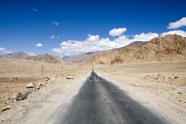 Narrow tar bituman road on the Leh-Kargil road stretch in the barren cold dsert landscape of Ladakh. India — Stock Photo