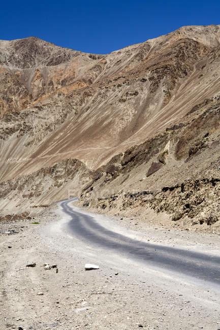 Carretera bituman de alquitrán estrecho en el tramo de carretera de Leh-Kargil en el paisaje estéril del dsert frío de Ladakh.India - foto de stock