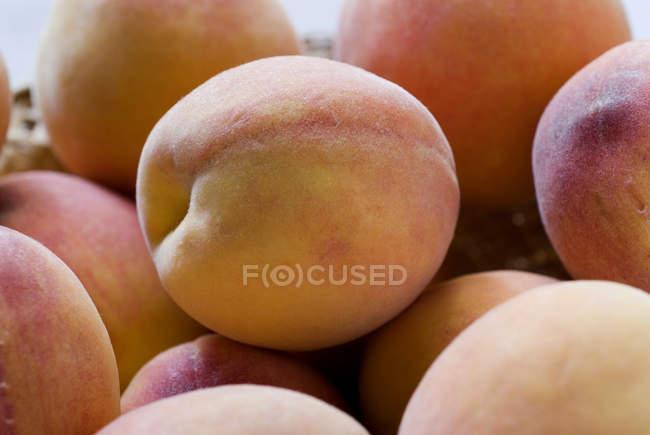 Pochi frutti di pesche in cestino sopra priorità bassa bianca vaga — Foto stock