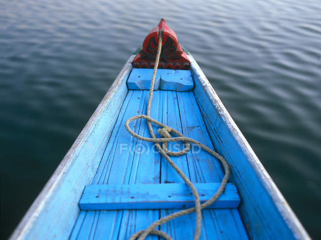 View of blue wooden boat over calm river water and rope inside — Stock Photo