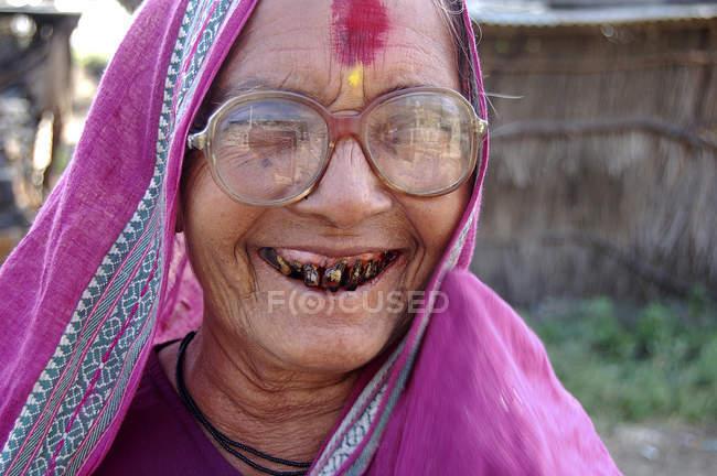 Усміхаючись сільська жінка з чорним зуби в рожевий Сарі. Salunkwadi, Ambajogai, Beed, штаті Махараштра, Індія — стокове фото