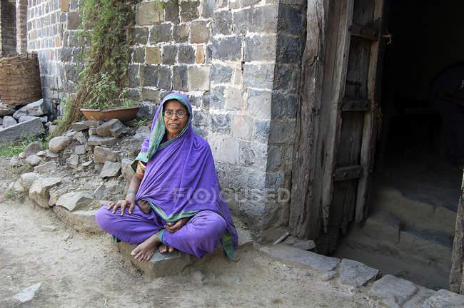 Rurale vieille femme indienne assis en face de la maison. Salunkwadi, Ambajogai, Maharashtra, Inde — Photo de stock