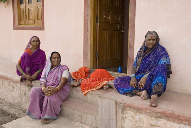 Tres damas descansando y una señora durmiendo frente a la casa. Salunkwadi, Ambajogai, Beed, Maharashtra, India - foto de stock