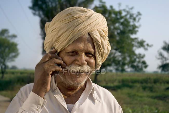 Agriculteur indien dans des vêtements nationales talking sur téléphone mobile, Salunkwadi, Ambajogai, Beed, Maharashtra, Inde — Photo de stock