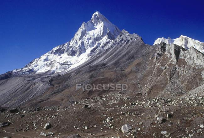 Vista delle cime di montagne con campo lapidato sulla pista durante il giorno — Foto stock