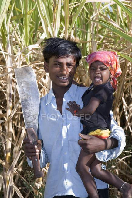 Індійська фермер з ножем і дитини в поле. Salunkwadi, Taluka, Ambejpgai район, Beed, штаті Махараштра, Індія — стокове фото